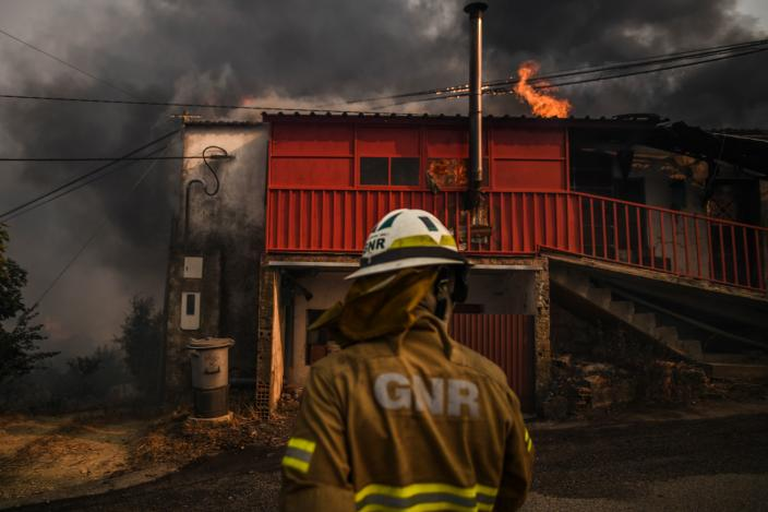 A National Guard Firefighter stands in front of a burning house at Roda village in Macao, central Portugal on July 21, 2019. (Photo: Patricia De Melo Moreira/AFP/Getty Images)