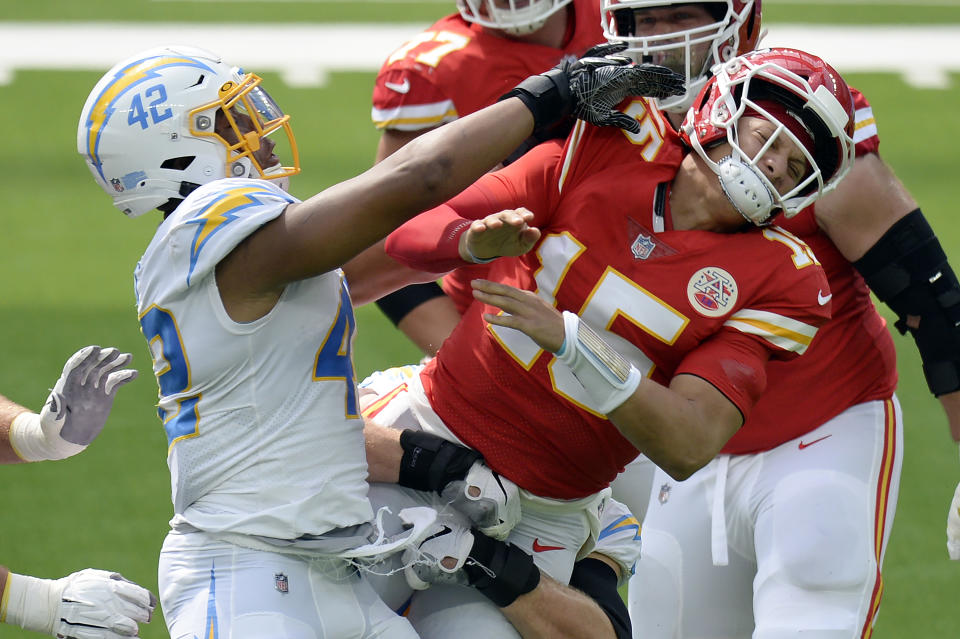Patrick Mahomes, right, is pressured by Uchenna Nwosu.