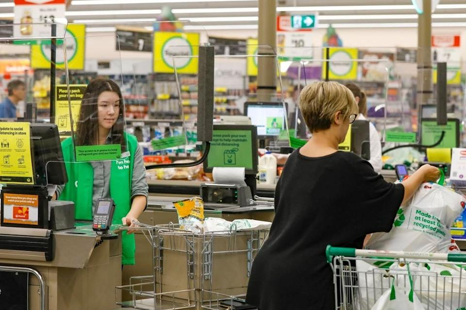 A Woolworths customer loads groceries into her trolley as a worker watches on. Source: Woolworths Group