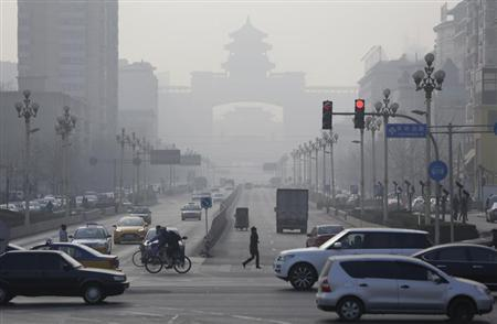 Pedestrians cross the road on a hazy day in Beijing