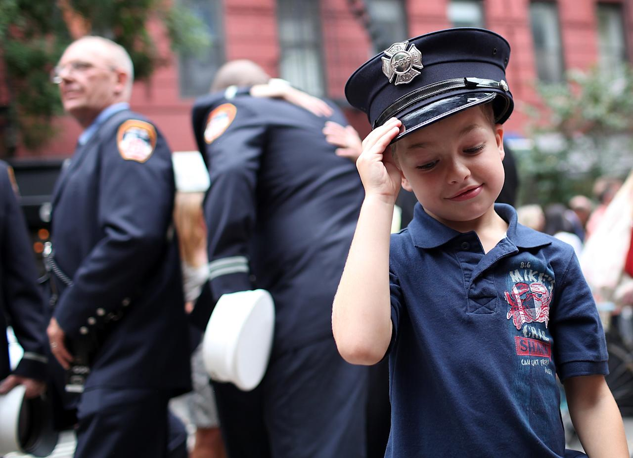 Six year-old Peter Samuelson wears a firefighter hat after a memorial service at Old St. Pat's Church to mark the tenth anniversary of the September 11 terror attacks on the World Trade Center on September 11, 2011 in New York City. New York City firefighters are commemorating the 10th anniversary of the 9/11 terrorist attacks and honoring the 343 firefighters who died in the line of duty. (Photo by Justin Sullivan/Getty Images)