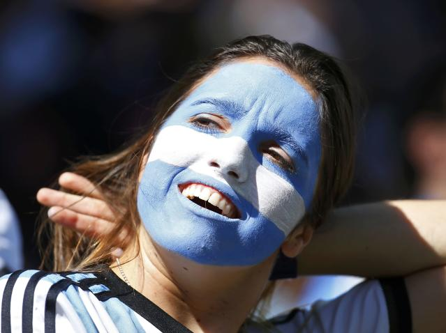 A fan of Argentina, with her face painted in the country's national colours, smiles before their 2014 World Cup round of 16 game against Switzerland at the Corinthians arena in Sao Paulo July 1, 2014. REUTERS/Paul Hanna (BRAZIL - Tags: SOCCER SPORT WORLD CUP)