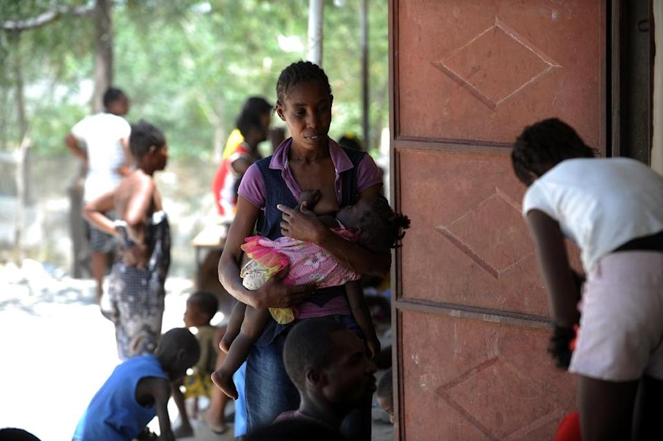 A Haitian mother holds her child at a school in Fond Parisien on July 3, 2015, after she was arrested and deported from the Dominican Republic (AFP Photo/Hector Retamal)