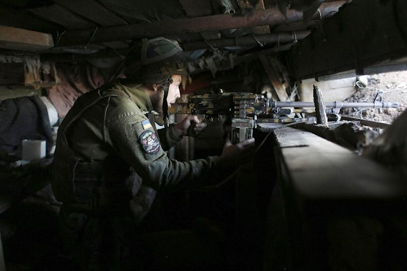 A Ukrainian serviceman monitors the positions of Russia-backed separatists