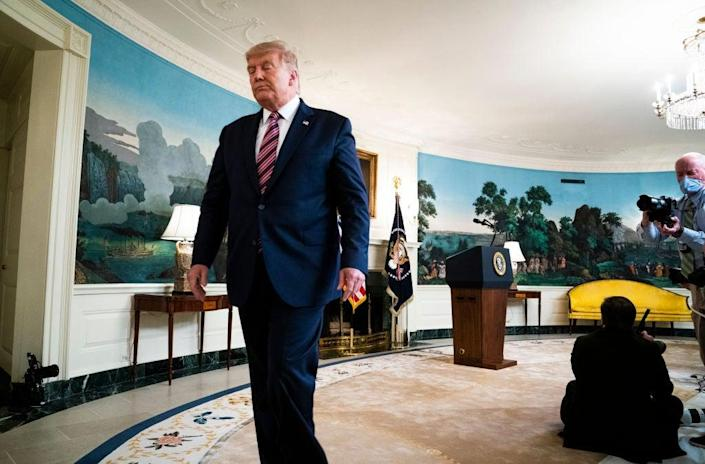 Donald Trump walks away from reporters after answering questions about revelations from Bob Woodward's new book about his presidency. (Getty Images)