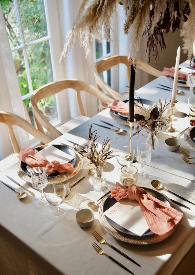 "<p>Use blush pink and navy blue for a modern take on a Thanksgiving table. The gold flatware adds a bit of festivity, while the dried florals bring a natural, laid-back touch. </p><p><a class=""body-btn-link"" href=""https://www.lifeslookingood.com/blog/rosh-hashanah-tablescape"" target=""_blank"">See more at Life's Looking Good</a></p>"