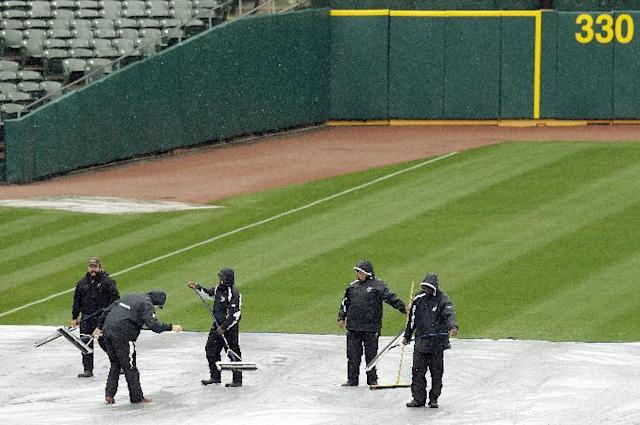 Workers remove water from a tarp covering the infield prior to an exhibition baseball game between the San Francisco Giants and the Oakland Athletics Saturday, March 29, 2014, in Oakland, Calif. (AP Photo/Ben Margot)