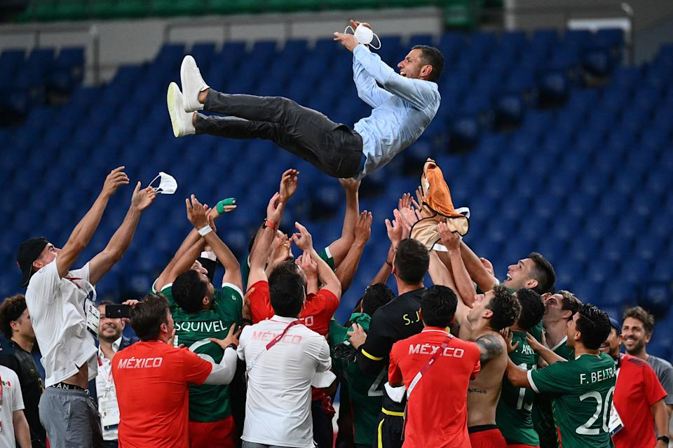 Mexico's players throw Mexico's coach Jaime Lozano into the air as they celebrate winning the Tokyo 2020 Olympic Games men's bronze medal football match between Mexico and Japan at Saitama Stadium in Saitama on August 6, 2021. (Photo by Vincenzo PINTO / AFP) (Photo by VINCENZO PINTO/AFP via Getty Images)