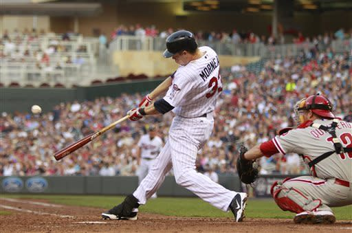 Minnesota Twins' Justin Morneau (33) hits an RBI double against Philadelphia Phillies as Humberto Quintero catches, right, during the fourth inning of a baseball game, Tuesday, June 11, 2013, in Minneapolis. (AP Photo/Genevieve Ross)
