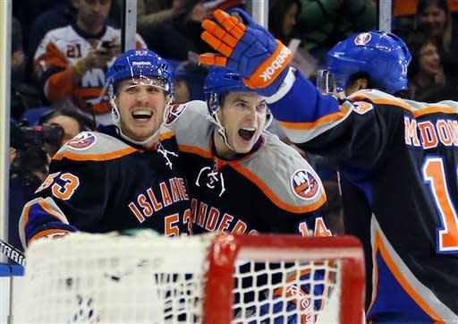 New York Islanders center Casey Cizikas (53), Thomas Hickey (14) and Colin McDonald (13) celebrate a goal by Cizikas during the second period of an NHL hockey game against the Washington Capitals at the Nassau Coliseum in Uniondale, N.Y., Saturday, March 9, 2013. (AP Photo/Paul J. Bereswill)