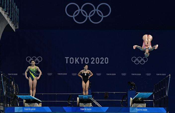 <p>Australia's Esther Qin (L) and Russia's Mariia Poliakova (C) wait as Switzerland's Michelle Heimberg competes in the women's 3m springboard diving final event during the Tokyo 2020 Olympic Games at the Tokyo Aquatics Centre in Tokyo on August 1, 2021. (Photo by Attila KISBENEDEK / AFP) (Photo by ATTILA KISBENEDEK/AFP via Getty Images)</p>