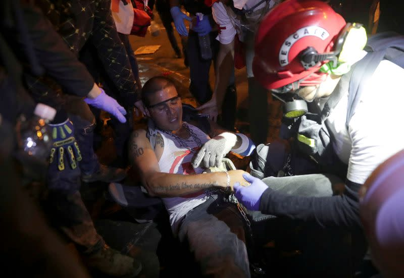 FILE PHOTO: An injured demonstrator is attended by paramedics during a clash with police during a protest against the decision of Congress to remove former President Martin Vizcarra, in Lima