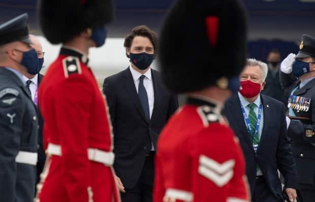 Prime Minister Justin Trudeau walks with Canadian High Commissioner to the United Kingdom Ralph Goodale through an honour guard as he arrives at the airport in Newquay, United Kingdom for the G7 Summit Thursday, June 10, 2021.