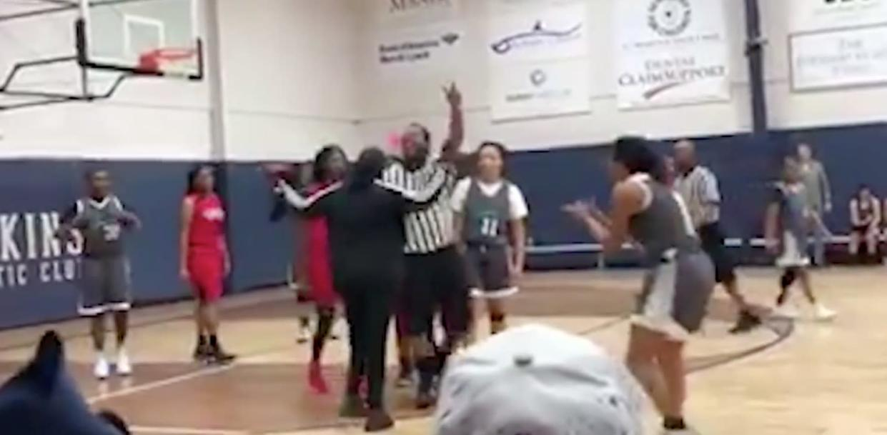 """A referee is harassed in this still from a video submitted to the """"Offside"""" Facebook group. (Image: Offside via Facebook.)"""