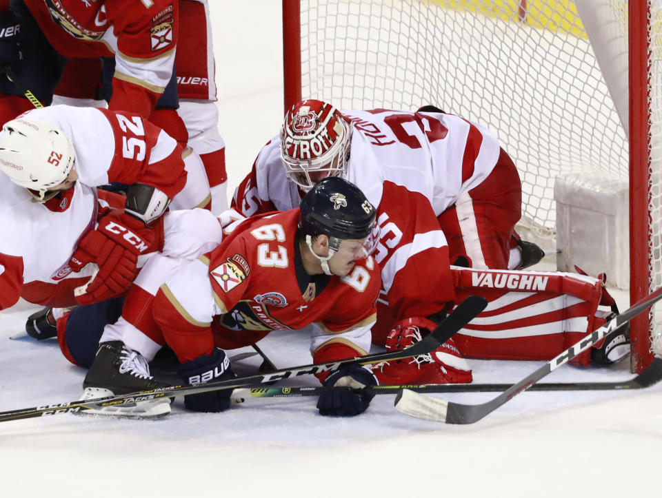Florida Panthers right wing Evgenii Dadonov (63) attempts to shoot past Detroit Red Wings goaltender Jimmy Howard (35) and defenseman Jonathan Ericsson (52) during the second period of an NHL hockey game, Sunday, March 10, 2019 in Sunrise, Fla. (AP Photo/Wilfredo Lee)