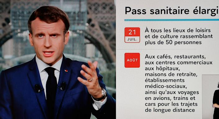 French President Emmanuel Macron is seen on a TV screen as he speaks during a televised address to the nation from the temporary Grand Palais in Paris on July 12, 2021. - Macron announced  mandatory Covid jabs for healthcare staff and that 'Covid pass' will be needed in restaurants from August. (Photo by Ludovic MARIN / AFP) (Photo by LUDOVIC MARIN/AFP via Getty Images)