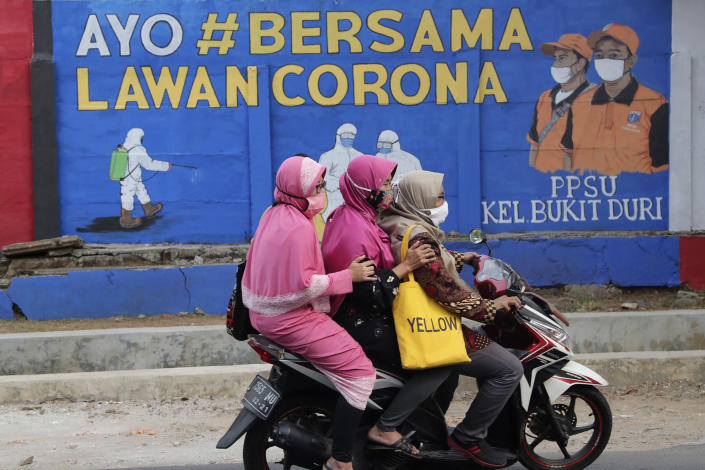 """Muslim women ride a motorbike past a coronavirus-themed mural in Jakarta, Indonesia, Thursday, Sept. 10, 2020. Writings on the mural read """"Let's fight coronavirus together"""". As companies race to develop a COVID-19 vaccine and countries scramble to secure doses, questions about the use of pork products — banned by some religious groups — has raised concerns about the possibility of disrupted immunization campaigns. (AP Photo/Tatan Syuflana)"""