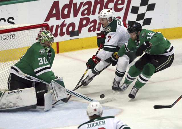 Dallas Stars goaltender Ben Bishop (30) and center Jason Dickinson (16) defend as Minnesota Wild center Nico Sturm (7) shoots in the second period of an NHL hockey game Saturday, April 6, 2019, in Dallas. (AP Photo/Richard W. Rodriguez)