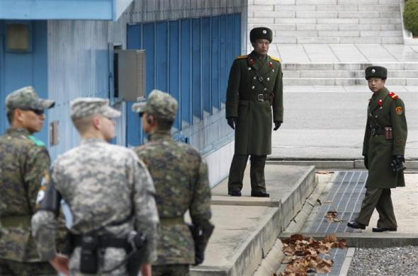 North Korean soldiers (top R) look across a concrete border as a U.S. army soldier (2nd L) and South Korean soldiers stand guard at the truce village of Panmunjom in the Demilitarized Zone (DMZ), in Paju, 55 km (34 miles) north of Seoul December 2, 2011.