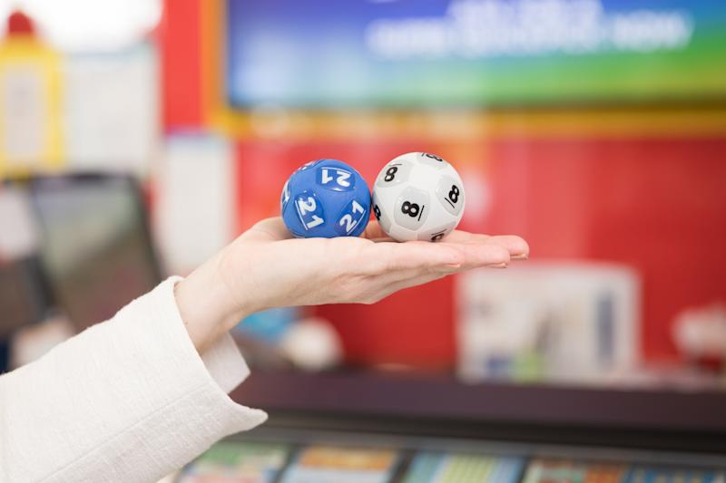 Photo shows two Powerball balls being held as Victorian entrant claims $80 million.