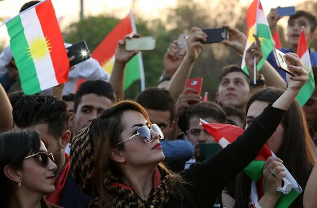 <p>An Iraqi Kurdish woman takes a selfie as people gather in the street flying Kurdish flags to urge fellow Kurds to vote in the upcoming independence referendum in Arbil, the capital of the autonomous Kurdish region of northern Iraq, Sept. 13, 2017. (Photo: Safin Hamed/AFP/Getty Images) </p>