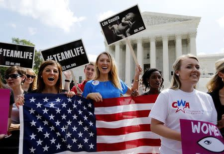 Anti-abortion protestors celebrate the U.S. Supreme Court's ruling striking down a Massachusetts law that mandated a protective buffer zone around abortion clinics, as the demonstrators stand outside the Court in Washington June 26, 2014. REUTERS/Jim Bourg