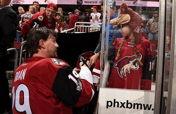 GLENDALE, AZ - MARCH 05: Shane Doan #19 of the Arizona Coyotes signs an autograph for a young fan after pre-game skate against the Carolina Hurricanes at Gila River Arena on March 5, 2017 in Glendale, Arizona. (Photo by Norm Hall/NHLI via Getty Images)