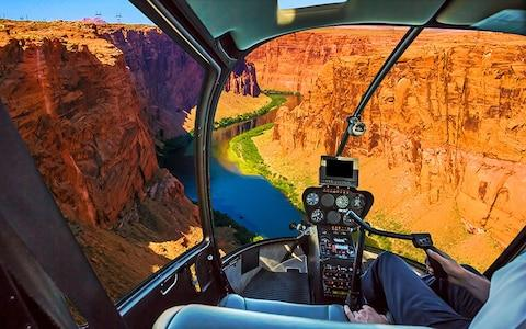 The view from inside a helicopter flying over Lake Powell within the Grand Canyon national park - Credit: AP