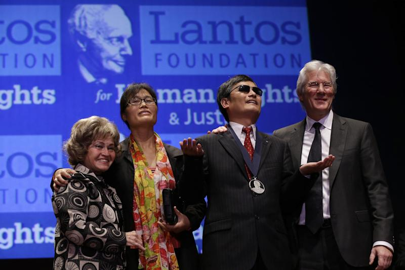 Actor Richard Gere, far right, stands with Chinese human rights activist Chen Guangcheng, as he reacts after being awarded the 2012 Tom Lantos Human Rights Prize on Capitol Hill in Washington, on Tuesday, Jan. 29, 2013. At left is Lantos' widow, Annette Lantos, and Guangcheng's wife, Yuan Weijing. (AP Photo/Jacquelyn Martin)