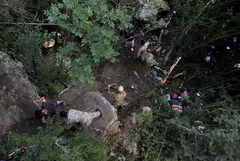 Emergency services attend the scene of a bus crash near Kolasin some 30 kilometers (18 miles) north of the capital Podgorica, Montenegro, Sunday, June 23, 2013. At least 13 people were killed and 32 were injured when a bus carrying Romanian tourists swayed off a bridge and plunged into a deep ravine in central Montenegro on Sunday, police said. The winding road that leads from Serbia in the north through the Moraca canyon and then to the seacoast is notorious for traffic accidents because it is narrow and slippery in wet weather conditions, and is considered one of the most dangerous to drive in the region. (AP Photo/Risto Bozovic)