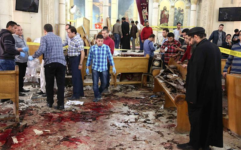 Security personnel and people looking at the aftermath following a bomb blast which struck worshippers gathering to celebrate Palm Sunday at the Mar Girgis Coptic Church in the Nile Delta City of Tanta, northen of Cairo, on April 9, 2017. - Credit: UPI / Barcroft Images