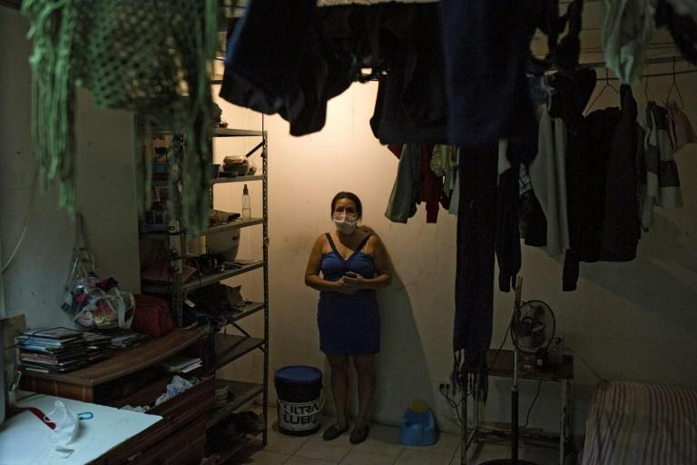 Norelis stands next to a bucket she uses as toilet in the room she where lives with her daughter, at a shelter located in the basement of the Sudameris public building in Caracas