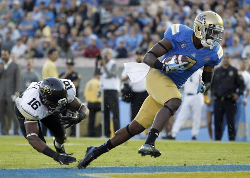 UCLA wide receiver Devin Fuller, right, gets away from Colorado defensive back Jeffrey Hall, left, to score in the first half of their NCAA college football game Saturday, Nov. 2, 2013, in Pasadena, Calif. (AP Photo/Alex Gallardo)