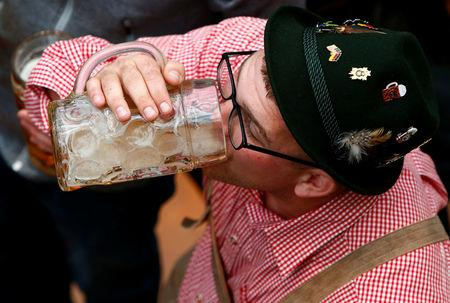 FILE PHOTO: A visitor drinks beer during the opening day of the 184th Oktoberfest in Munich, Germany, September 16, 2017. REUTERS/Michaela Rehle/File Photo