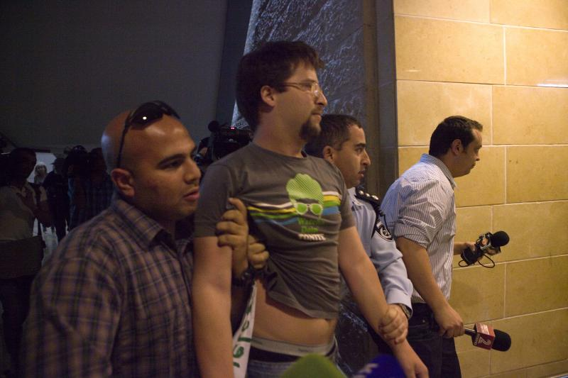 "An Israeli left-wing activists is detained by police at Ben Gurion Airport near Tel Aviv, Israel, Sunday, April 15, 2012. Four Israeli were arrested for causing a disturbance at the main airport terminal after unfurling a banner bearing the theme of the protest, ""Welcome to Palestine,"" a police spokesman said. Israel deployed hundreds of police Sunday at its main airport to detain activists flying in to protest the country's occupation of Palestinian areas, defying vigorous Israeli government efforts to block their arrival.(AP Photo/Dan Balilty)"