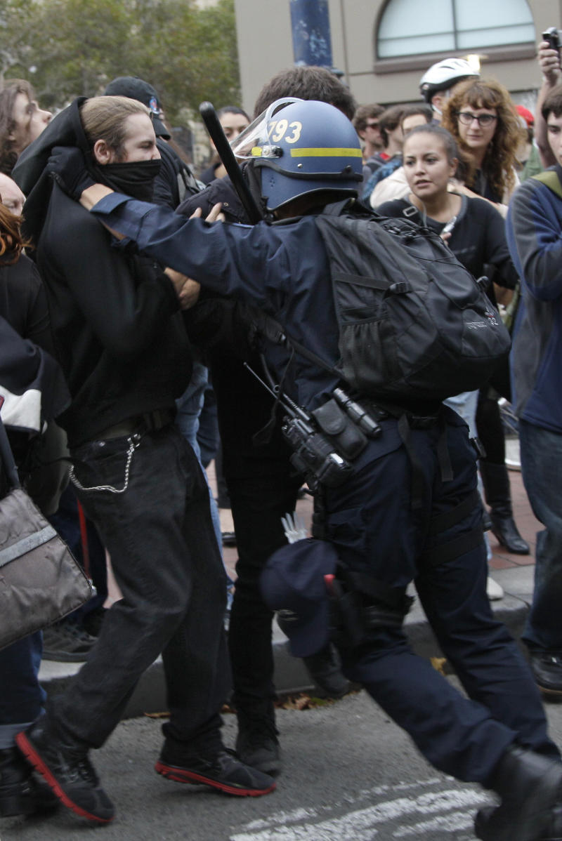 A San Francisco Police officer pushes protesters onto a sidewalk from Market Street in San Francisco, Monday, Aug. 22, 2011.   About 100 demonstrators on Monday were protesting the Bay Area Rapid Transit agency's decision to cut wireless service in its San Francisco stations earlier this month.  (AP Photo/Jeff Chiu)