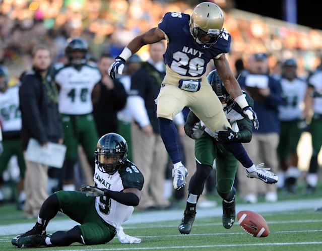 Navy's Darius Staten (26) looks for the loose ball after Hawaii's Donnie King Jr. (49) fumbled in the first half of an NCAA college football game on Saturday, Nov. 9, 2013, in Annapolis, Md. (AP Photo/Gail Burton)