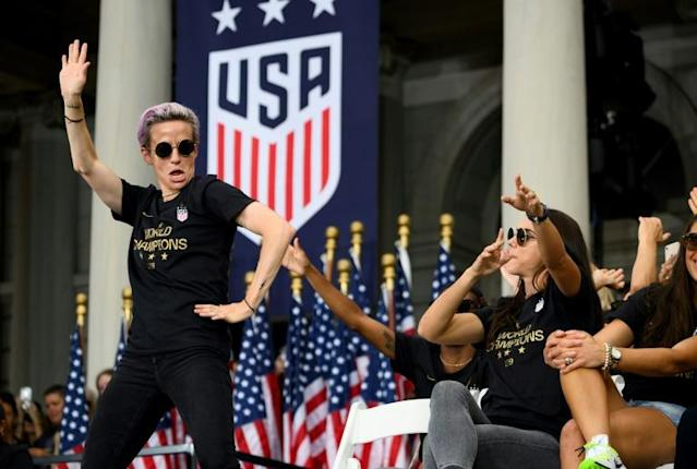 US women's soccer star Megan Rapinoe, left, and her teammates won a court ruling Friday in their fight for equal pay from the US Soccer Federation (AFP Photo/Johannes EISELE)