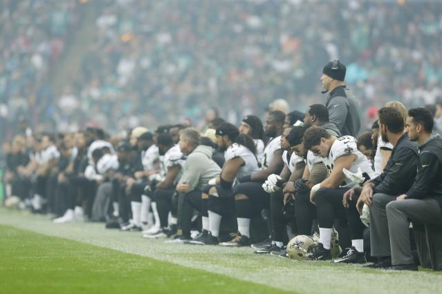 New Orleans Saints players kneel before the anthem is played at a game in London. (Getty Images)