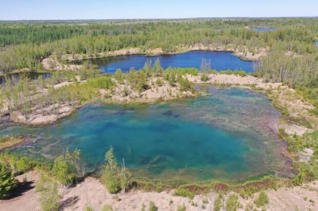 Several bodies of water at a former coal mining site just outside Minto appear turquoise in colour. (Shane Fowler/CBC - image credit)