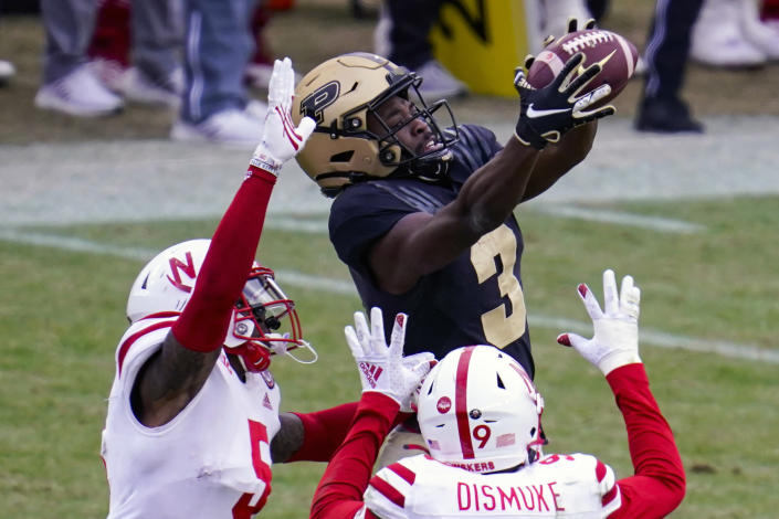 FILE - Purdue wide receiver David Bell (3) makes a catch over Nebraska safety Marquel Dismuke (9) and cornerback Cam Taylor-Britt (5) on his way to an 89-yard touchdown during the fourth quarter of an NCAA college football game in West Lafayette, Ind., in this Saturday, Dec. 5, 2020, file photo. With his knack for making the difficult catches as well as the easy ones, Bell is among the most dependable receivers in the country. (AP Photo/Michael Conroy, File)