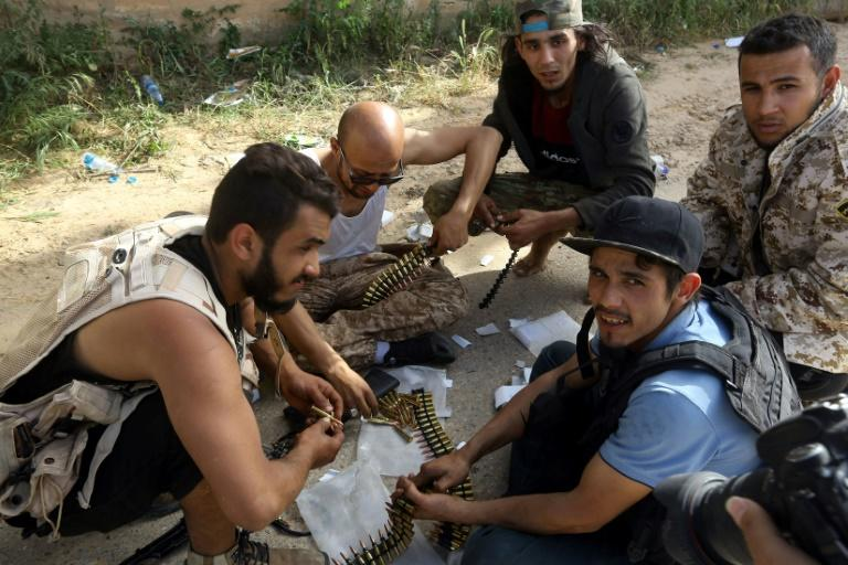Fighters loyal to the Government of National Accord sort ammunition belts during clashes with Haftar's forces on Saturday