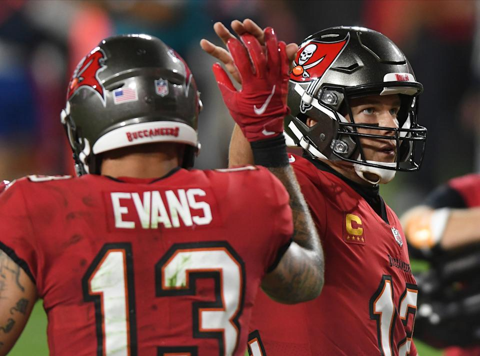 Tampa Bay Buccaneers quarterback Tom Brady (12) high fives wide receiver Mike Evans (13) after a touchdown against the Kansas City Chiefs during the second half of an NFL football game Sunday, Nov. 29, 2020, in Tampa, Fla. (AP Photo/Jason Behnken)