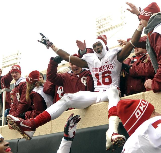 Oklahoma Wide Receiver Jaz Reynolds celebrates with fans after their 34-24 win over Oklahoma State in an NCAA college football game in Stillwater, Okla., Saturday, Dec. 7, 2013. (AP Photo/Brody Schmidt)