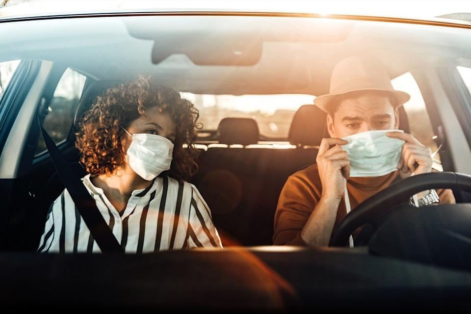 Coronavirus pandemic concept. breathing through a medical mask because of the danger of getting the flu virus, influenza infection. Enjoying travel. Beautiful young couple sitting on the front passenger seats and smiling while handsome man driving a car