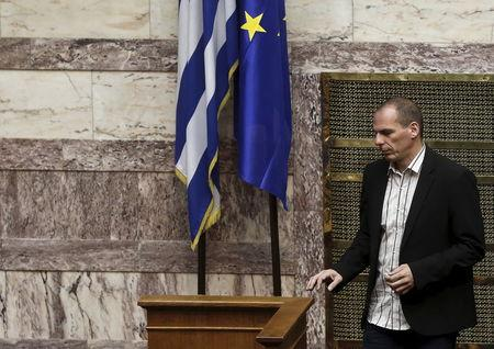 Greek Finance Minister Varoufakis walks next to an EU and a Greek national flag during a parliamentary session in Athens