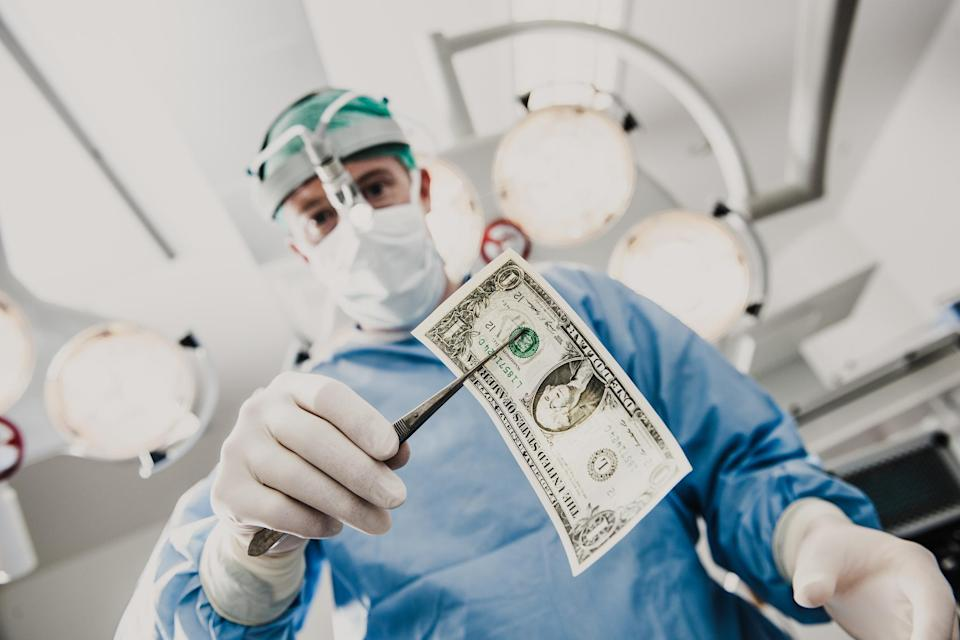 Surgeon removing a dollar bill from a patient.