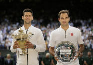 FILE - Serbia's Novak Djokovic, left, and Switzerland's Roger Federer pose with the trophies after the men's singles final match of the Wimbledon Tennis Championships in London, in this Sunday, July 14, 2019, file photo. There are plenty of intriguing story lines to follow on the grass courts. That includes Novak Djokovic's bid to equal Roger Federer and Rafael Nadal at 20 major titles and Serena Williams seeking her 24th. (AP Photo/Tim Ireland, File)