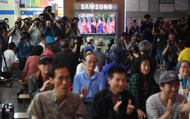 <p>People watch a television screen showing live footage of the summit between US President Donald Trump and North Korean leader Kim Jong Un in Singapore, at a railway station in Seoul on June 12, 2018. (Photo: Jung Yeon-je/AFP/Getty Images) </p>
