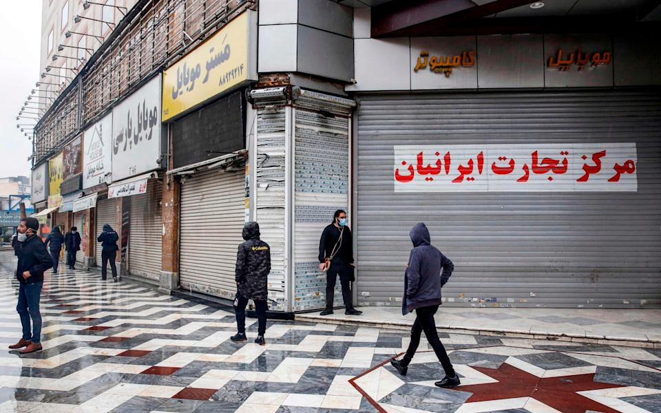 Mask-clad pedestrians walk past closed shops in Iran's capital Tehran as the Iranian government announced new coronavirus restrictions - AFP
